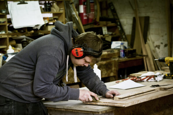 An employee wearing ear defenders while working