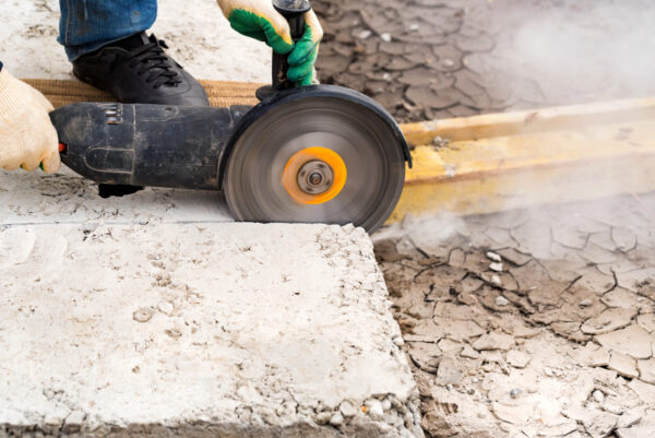 Construction worker cutting concrete with large abrasive wheel