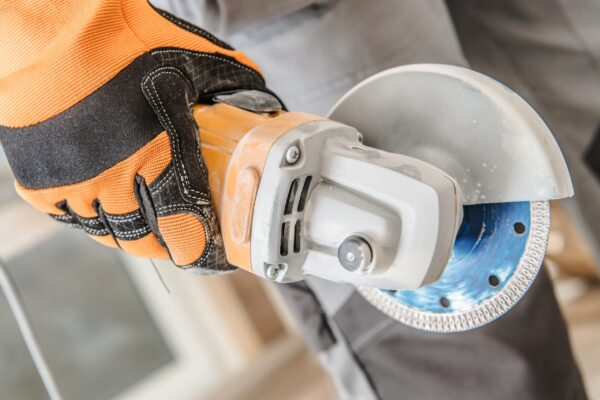Construction worker with small handheld circular saw.