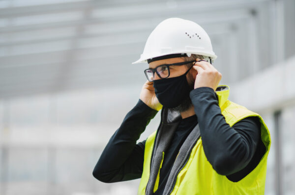 Employee checking worksite wearing a high vis jacket and a construction hat